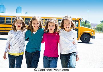 school girls friends in a row walking from school bus -...