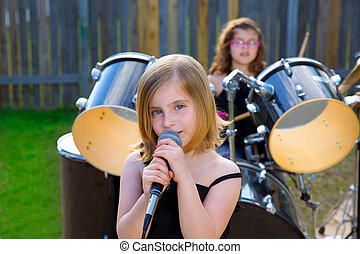 Blond kid girl singing in tha backyard with drums behind