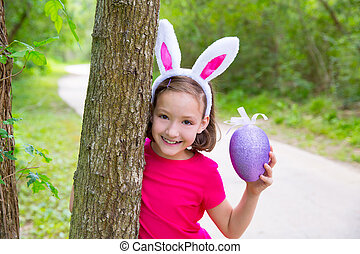 Easter girl with big purple egg and funny bunny ears on the...