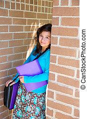 Schoolgirl teenager at school brick wall happy