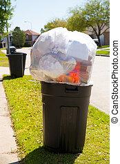 Trash bin dustbin full of garbage on street lawn
