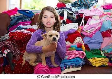 girl sitting on a messy clothes sofa with chihuahua dog