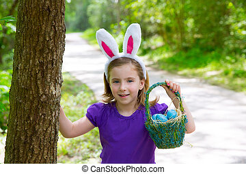 Easter girl with eggs basket and funny bunny ears on the...