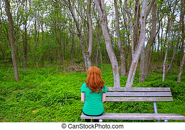 Lonely woman rear view looking to forest sitting on bench -...