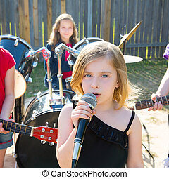 children singer girl singing playing live band in backyard -...