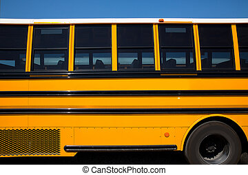 American typical school bus side view on blue sky day