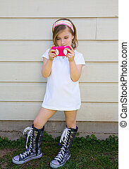 blond little fashion kid girl playing with smartphone