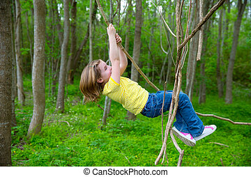 girls playing hanging in vines at the jungle park