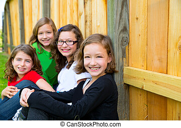 Girls group in a row smiling in a wooden fence - Grills...