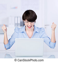 Excited businesswoman rejoicing at her success cheering and...
