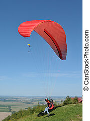 Taking off - Paraglider with red parachute taking off from...
