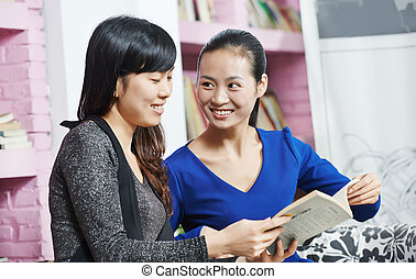 young chinese girls with book in library - Smiling chinese...