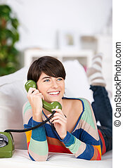 Woman on telephone - Smiling woman talking through the green...