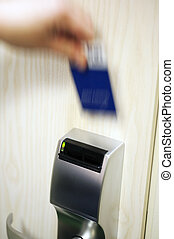 Open hotel door - A blurry hand with a keycard, opening the...