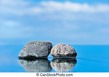 Two stones input - Stones on a smooth surface against the...