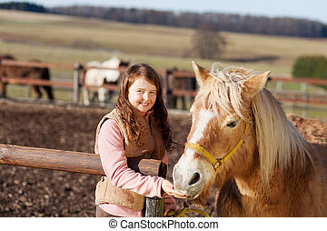 Portrait of a smiling girl with her horse