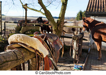 Horse saddle on top of a wooden fence