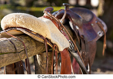 Close-up of a horse saddle on top of a fence - Close-up of a...