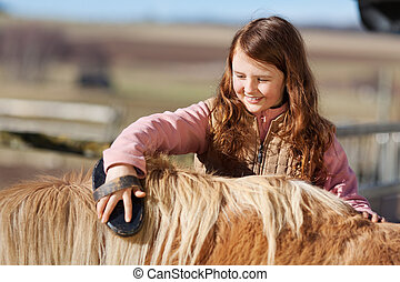 Teenager brushing her pet pony - Cute pretty little teenage...