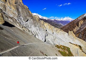 Trekker in red jacket in Himalayas mountains - Trekker in...