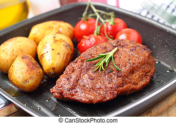 Veggie-Steak with baked potatoes and grilled tomatoes