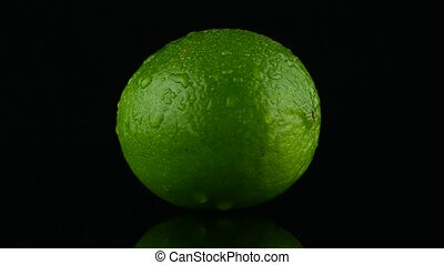 Green lime rotating on black reflective background.