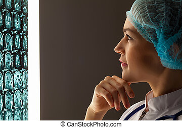 Woman doctor examining x-ray - Image of attractive woman...