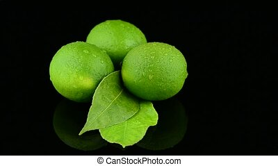 Fresh green limes rotating on black reflective background