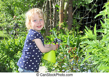 Gardening - Happy child in garden sprays roses