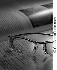 glasses on a book black and white
