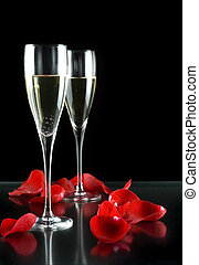 champagne glass with petals of rose isolated on black...