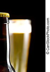 beer bottle and glass isolated on black background