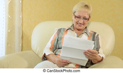 woman reading some financial paper - Cheerful senior woman...
