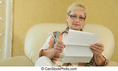 woman looking at a bank statement - Mature woman looking at...