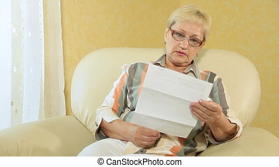 Woman at Home with Bills - Senior woman reading some...
