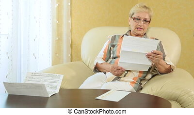 Woman looking over financial papers - Mature woman looking...