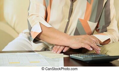 Mature woman calculating taxes