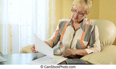 Calculating taxes - Mature woman calculating taxes at home
