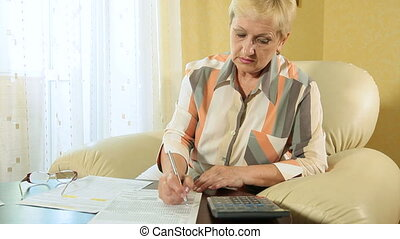 Senior woman calculating taxes