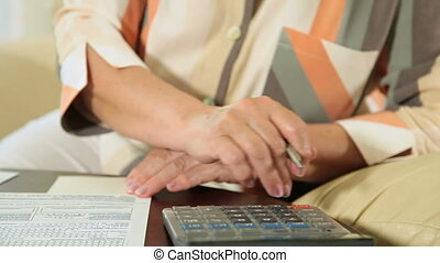 Female hands filling tax form - Hands of mature woman fills...