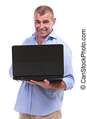 casual middle aged man holding his laptop - casual senior...