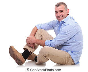 casual middle aged man sits and smiles at you - side view of...