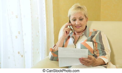 Mature woman calling by the phone - Mature woman sitting in...