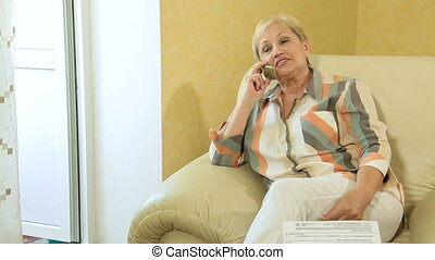 Mature woman talking on phone - Mature woman sitting in...