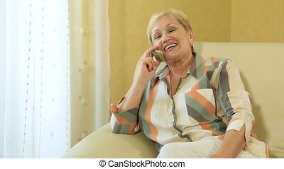 Cheerful mature woman on the phone at home