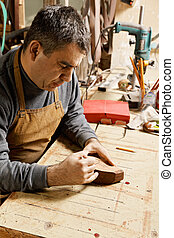 Artisan in workshop drawing on billet - Artisan in workshop...