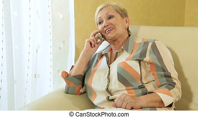 Lively conversation on the phone - Mature woman busy...
