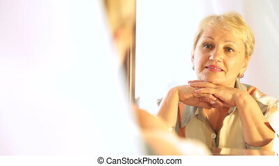 Senior woman looking into mirror