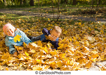 Young children playing in autumn leaves