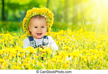Beautiful happy little baby girl in a wreath on a meadow...